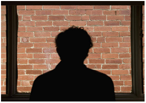 Brick Wall with shadow of person framed in the center